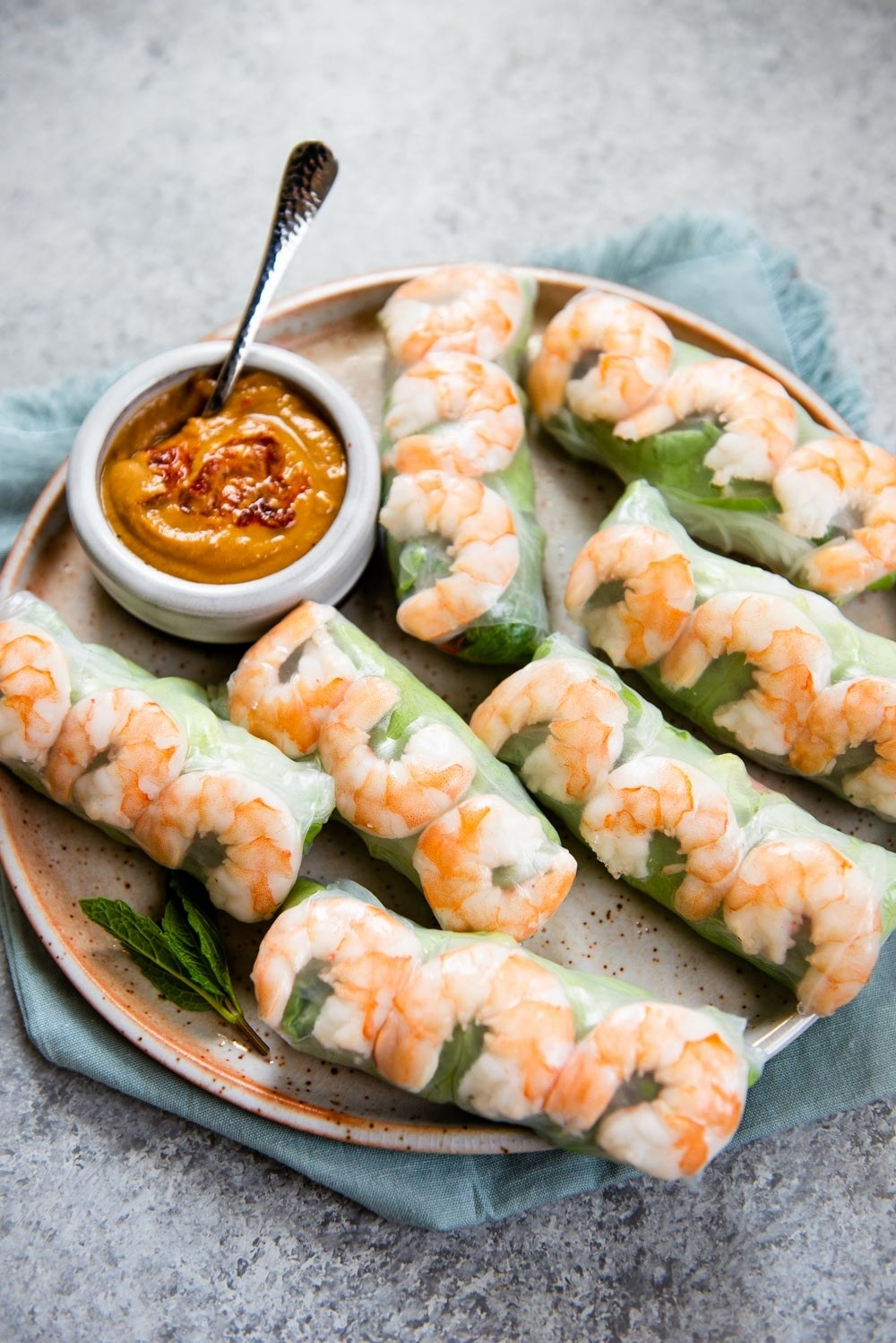 A plate of spring rolls, tightly wrapped and see through so plump shrimp and greens show; a small bowl of a spicy and creamy peanut sauce sits beside them