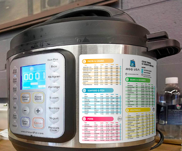An Instant Pot with the cheat sheet on the side showing pasta, seafood, pork, beans, and vegetable timing