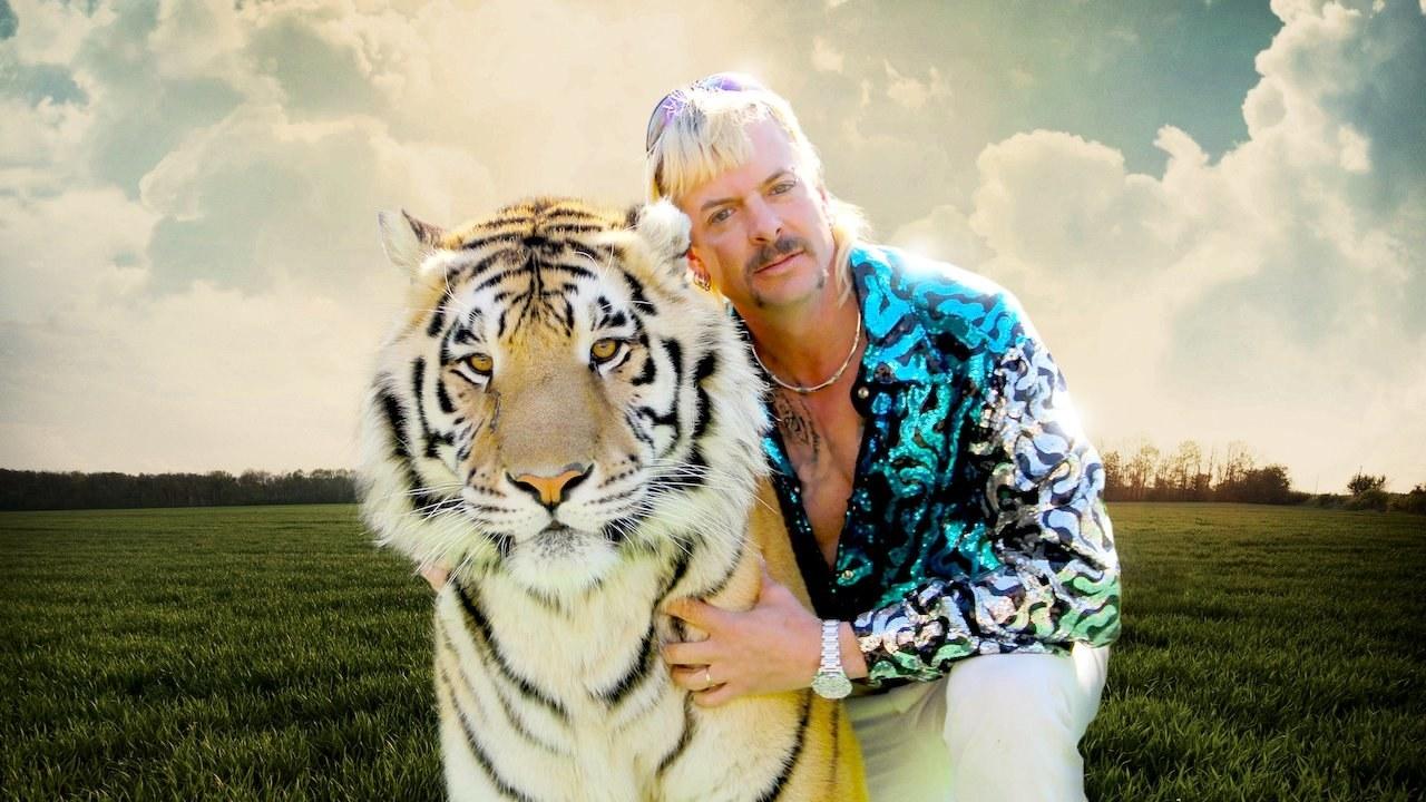 Hombre con pelo rubio abrazando a un tigre en un campo