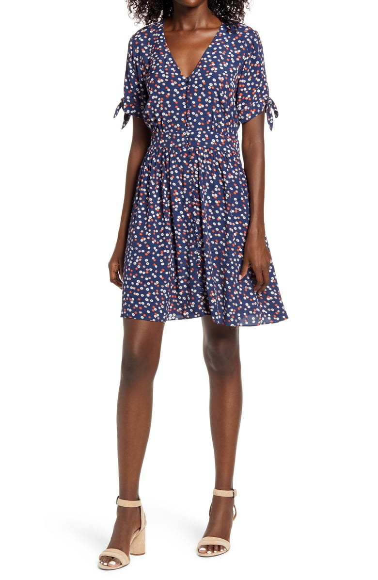 Model wearing the button-front dress with cute ties on the short sleeves in a blue floral pattern