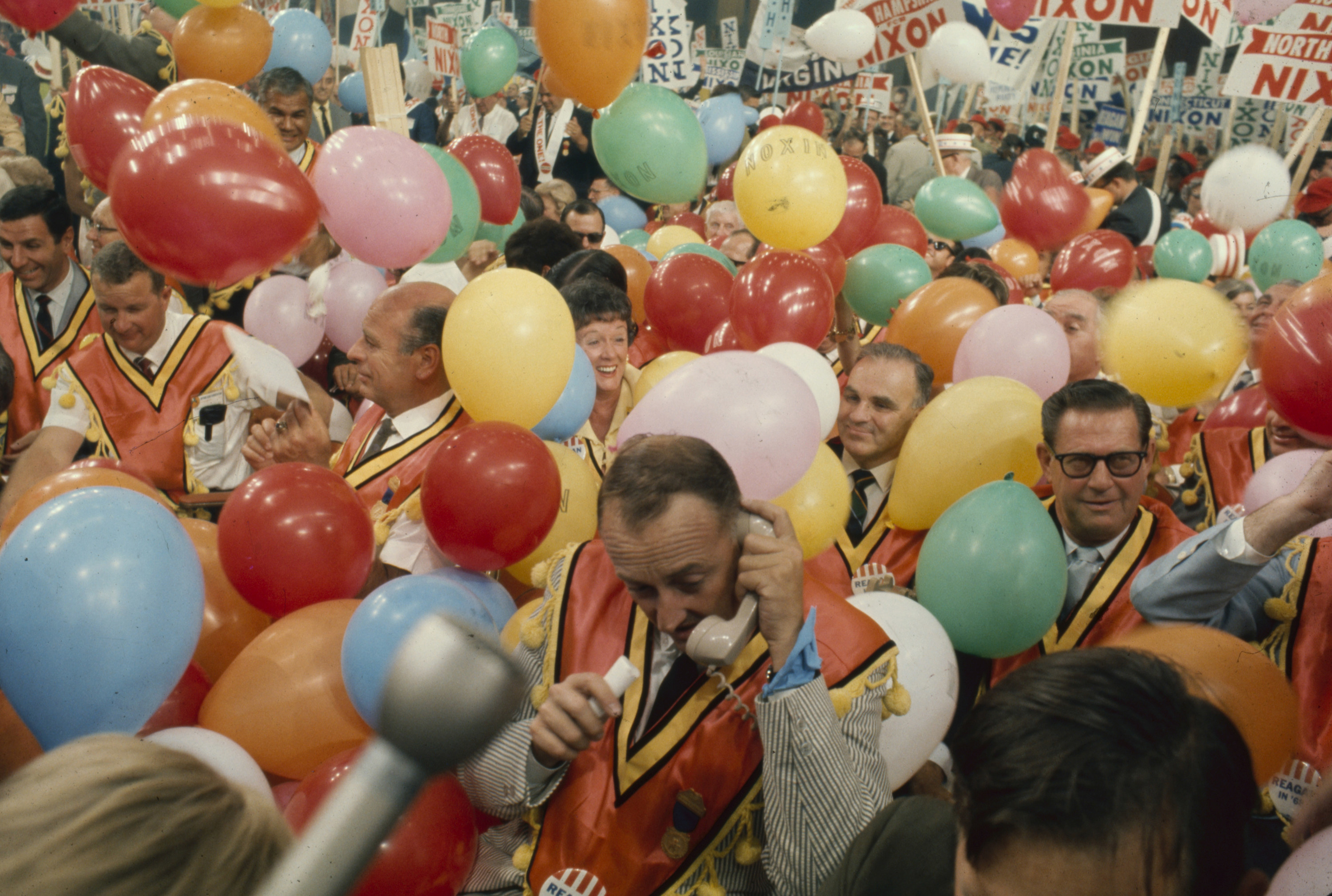 A man on a phone amidst a sea of balloons