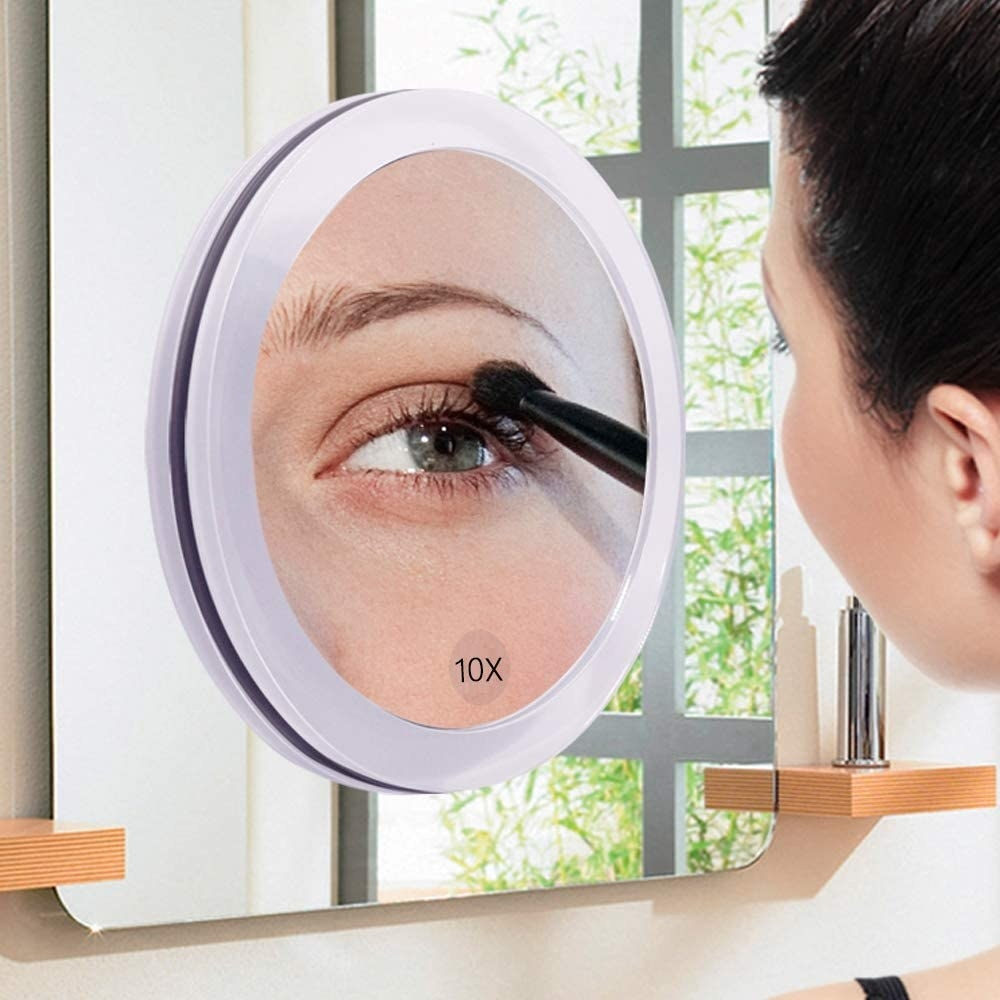 A person doing their eyeshadow in the magnifying mirror