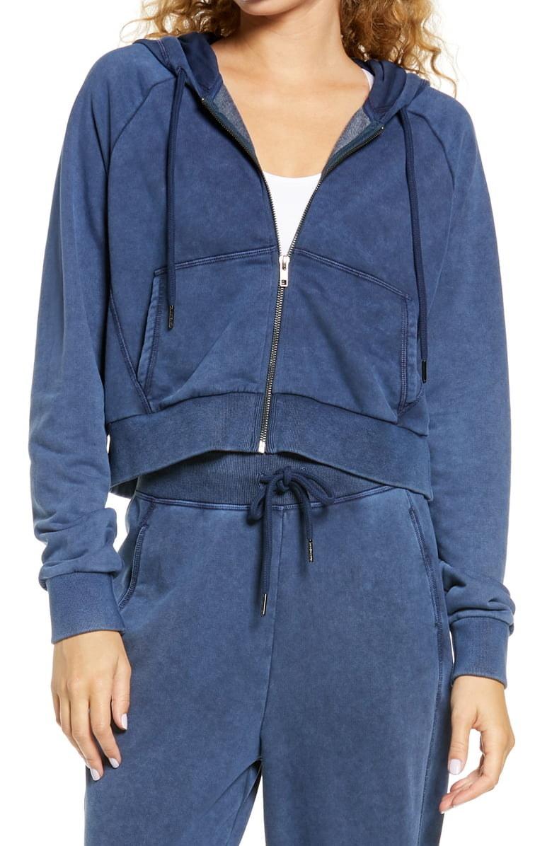 Model wearing Sweaty Betty Gary zip front hoodie in beetle blue