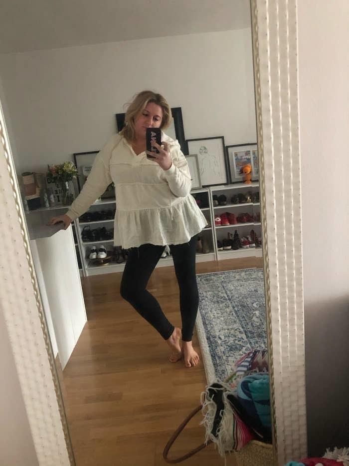 BuzzFeed writer Elena Garcia wearing the black leggings with a white blouse while taking a mirror selife