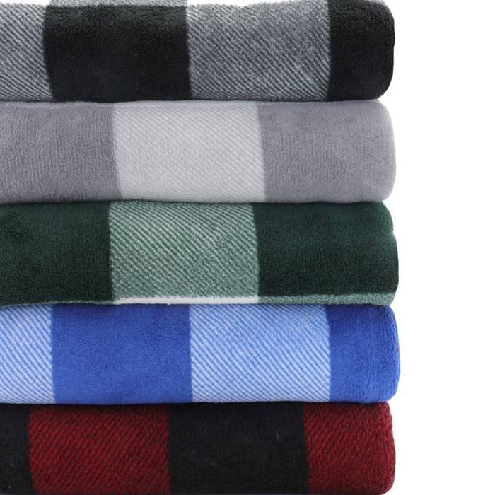 A stack of five folded fleece blankets in different plaid colors