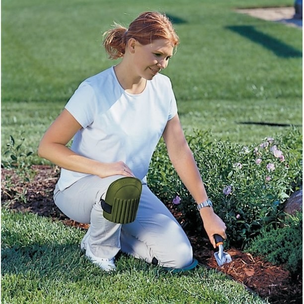Model wearing green knee pads while tending to garden