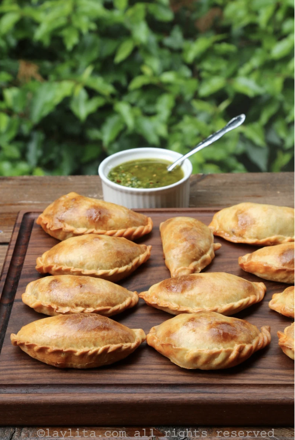 In front of a blurred background of greenery, a wooden board holds brown and crispy empanadas with crimped edges while a small bowl holds a vibrant green dipping sauce