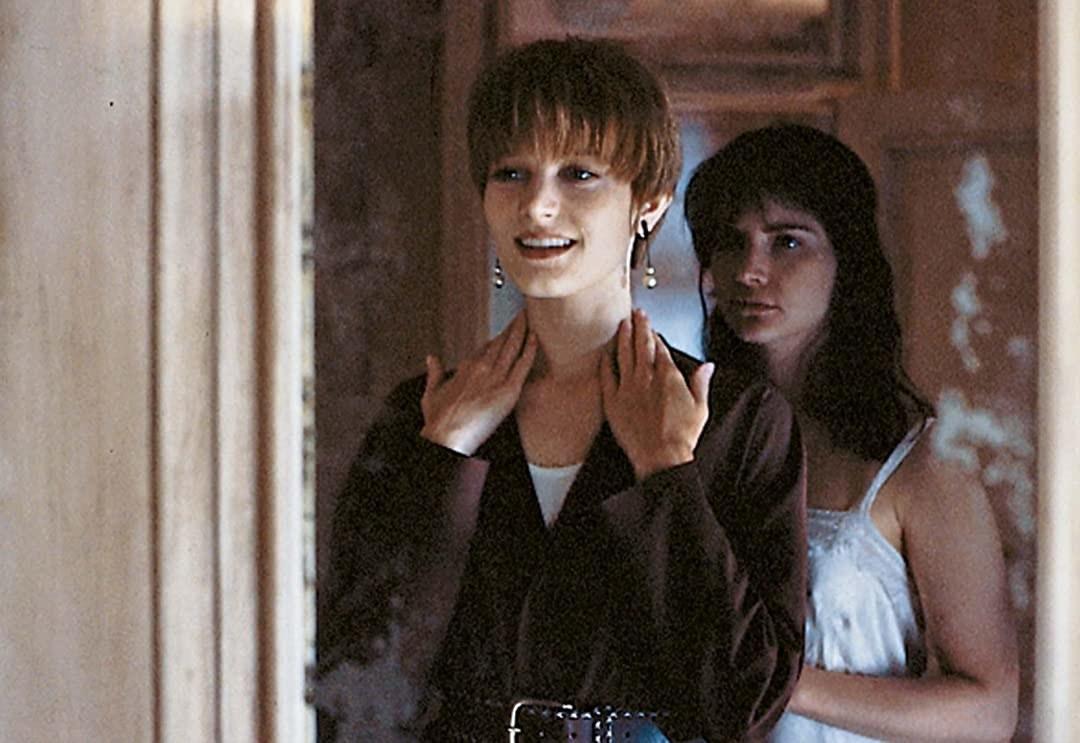 Mujer con cabello corto mirando el espejo y mujer con cabello negro largo detrás de ella