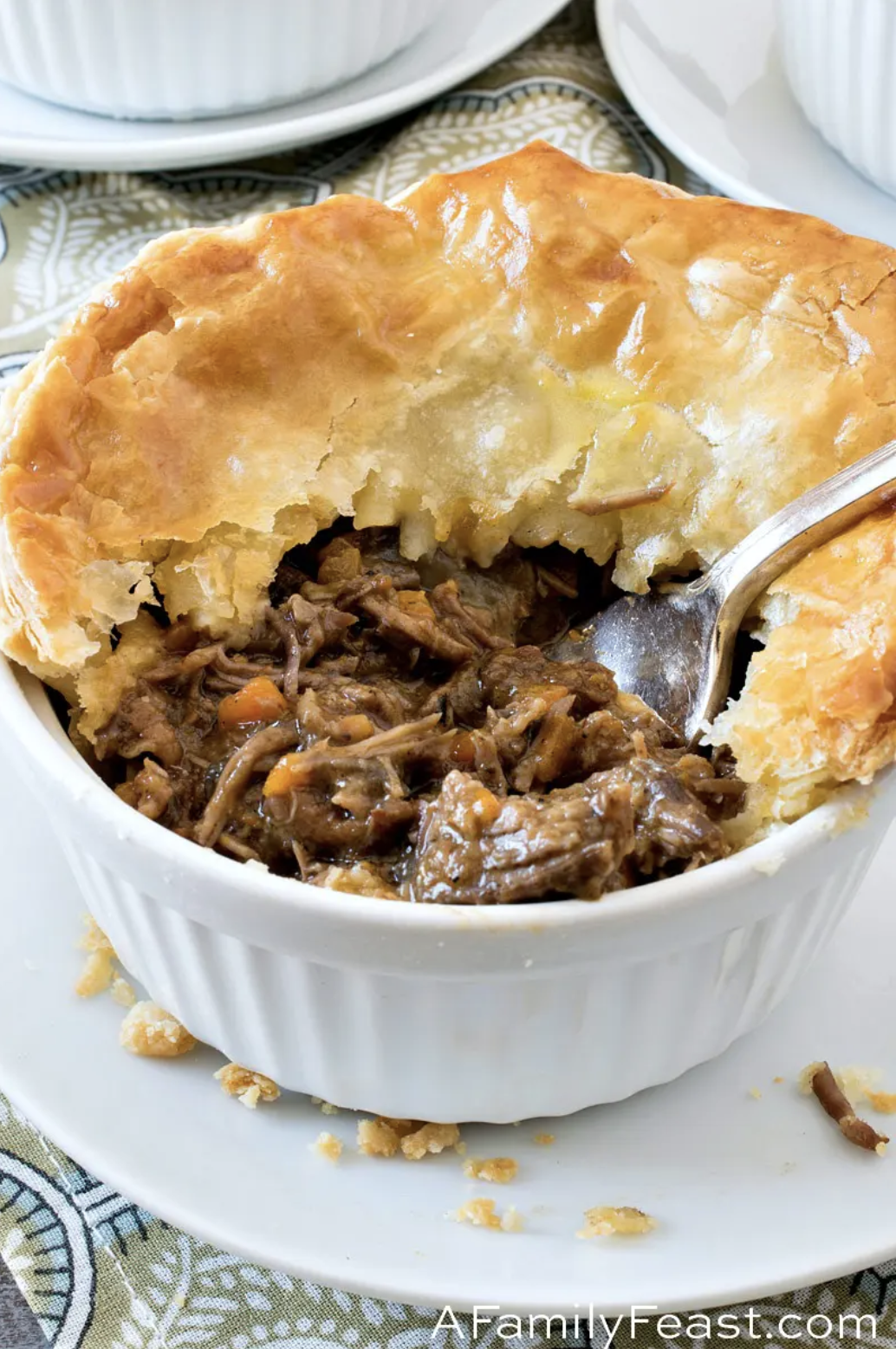 A white ramekin holds a meat pie, its crispy, flaky crust broken through to expose tender shredded beef in a thick, rich sauce