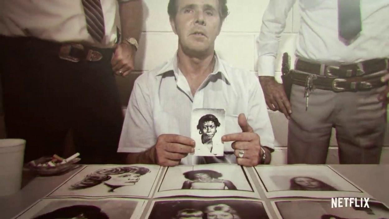 Hombre sosteniendo la foto de una mujer con fotos de mujeres en la mesa y policías detrás de él