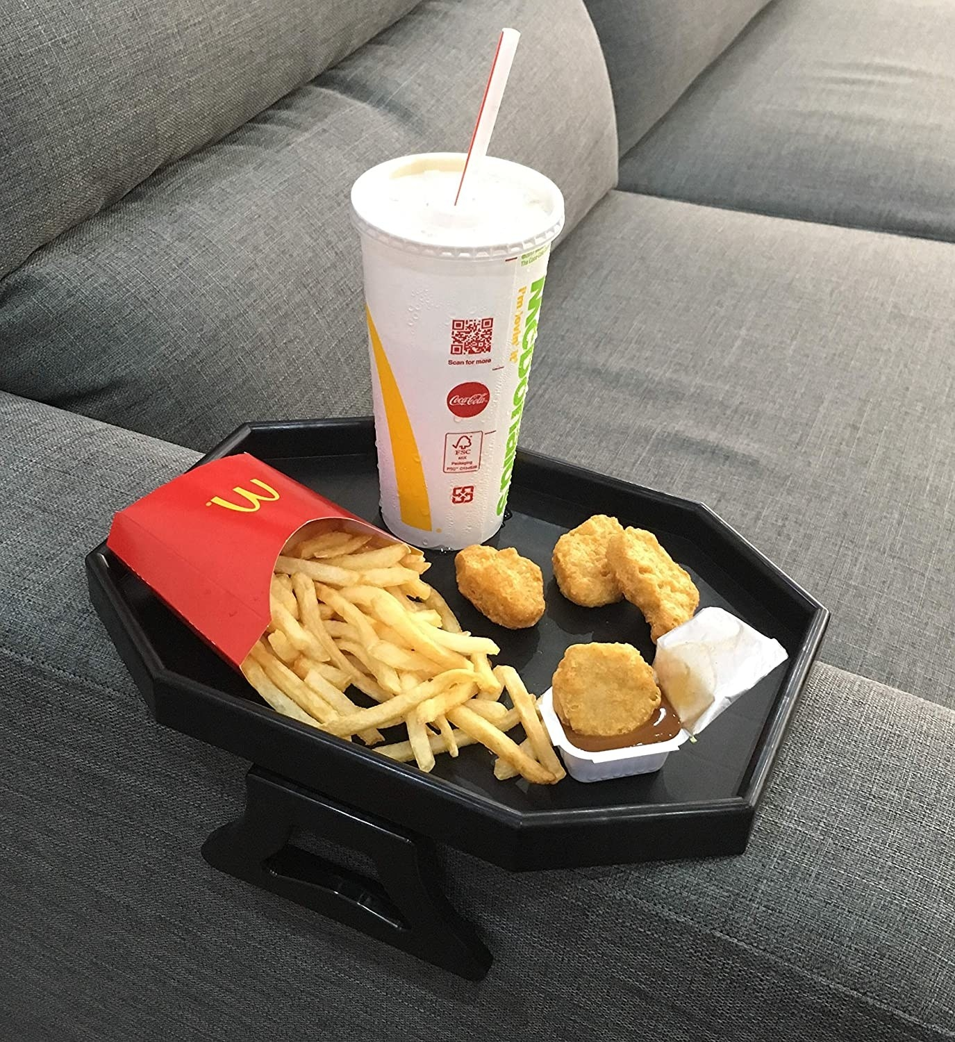 Fries, chicken nuggets, and a drink on top of the arm rest tray