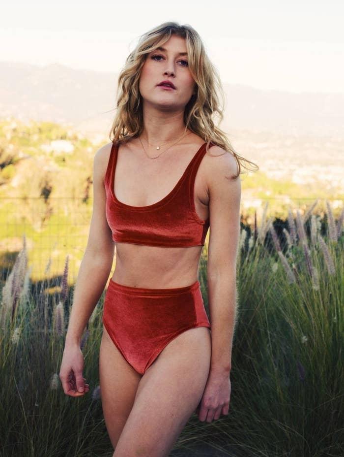 A model wearing the scoop neck, high-waisted red velvet bikini