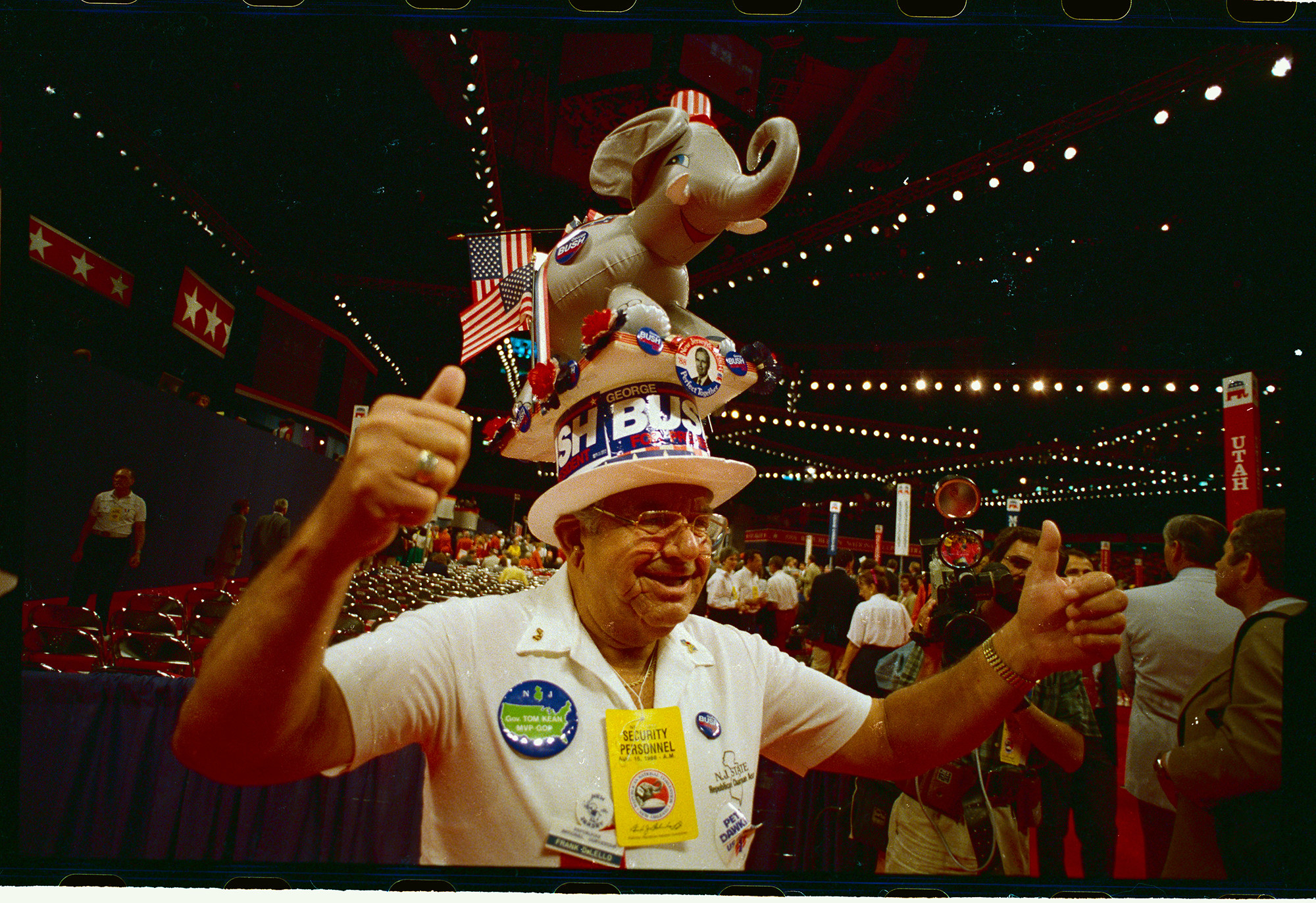 An older man wtih a hat that has an elephant on top that says bush  gives the thumbs up