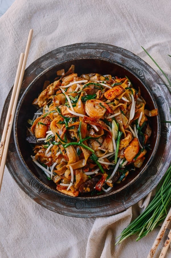 A bowl of wide noodles, shrimp, and a mix of crunchy veggies mixed with a sticky, spicy-looking glaze of sauce