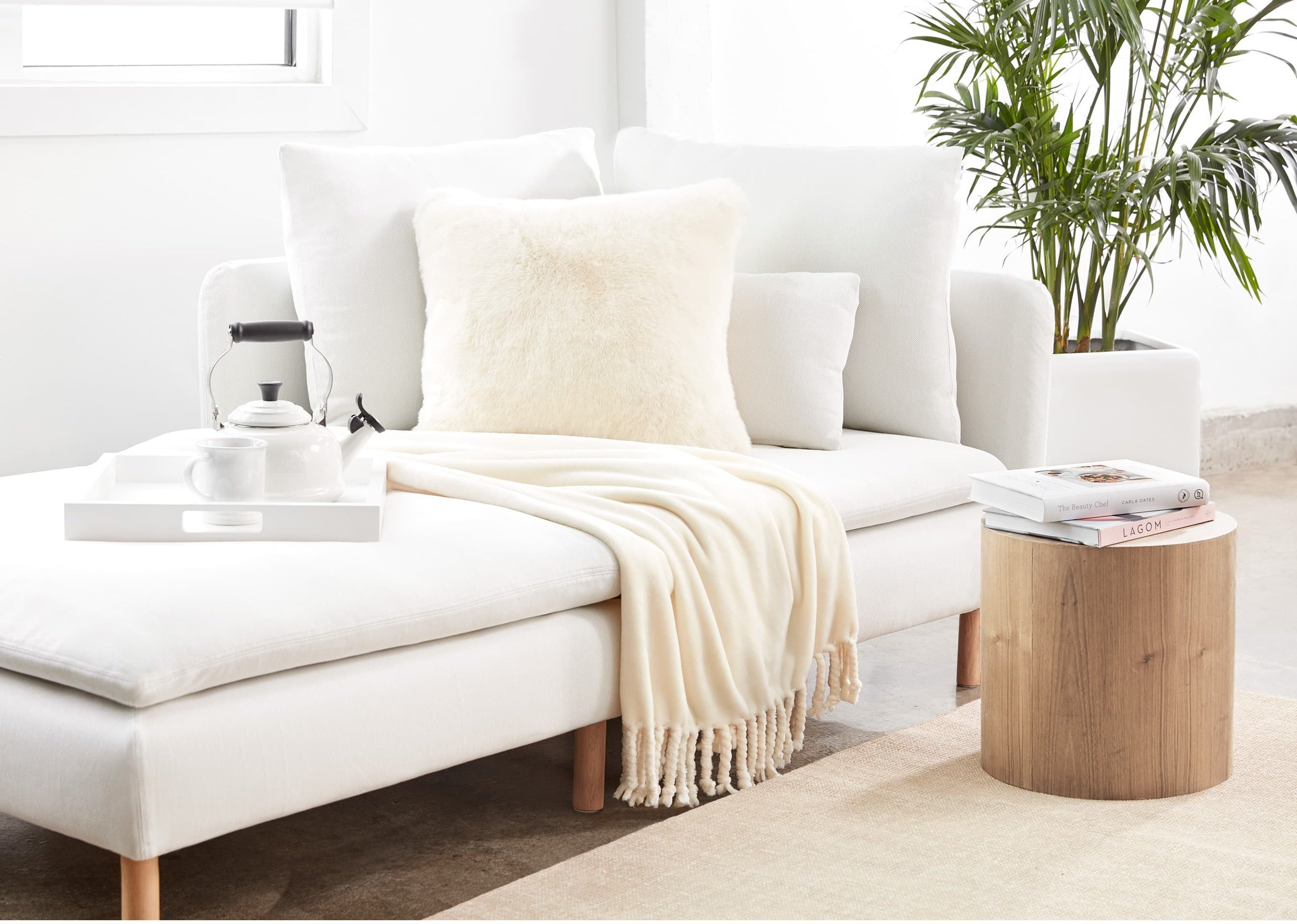 The vanilla Nordstrom Bliss Plush Throw on a chaise in a living room