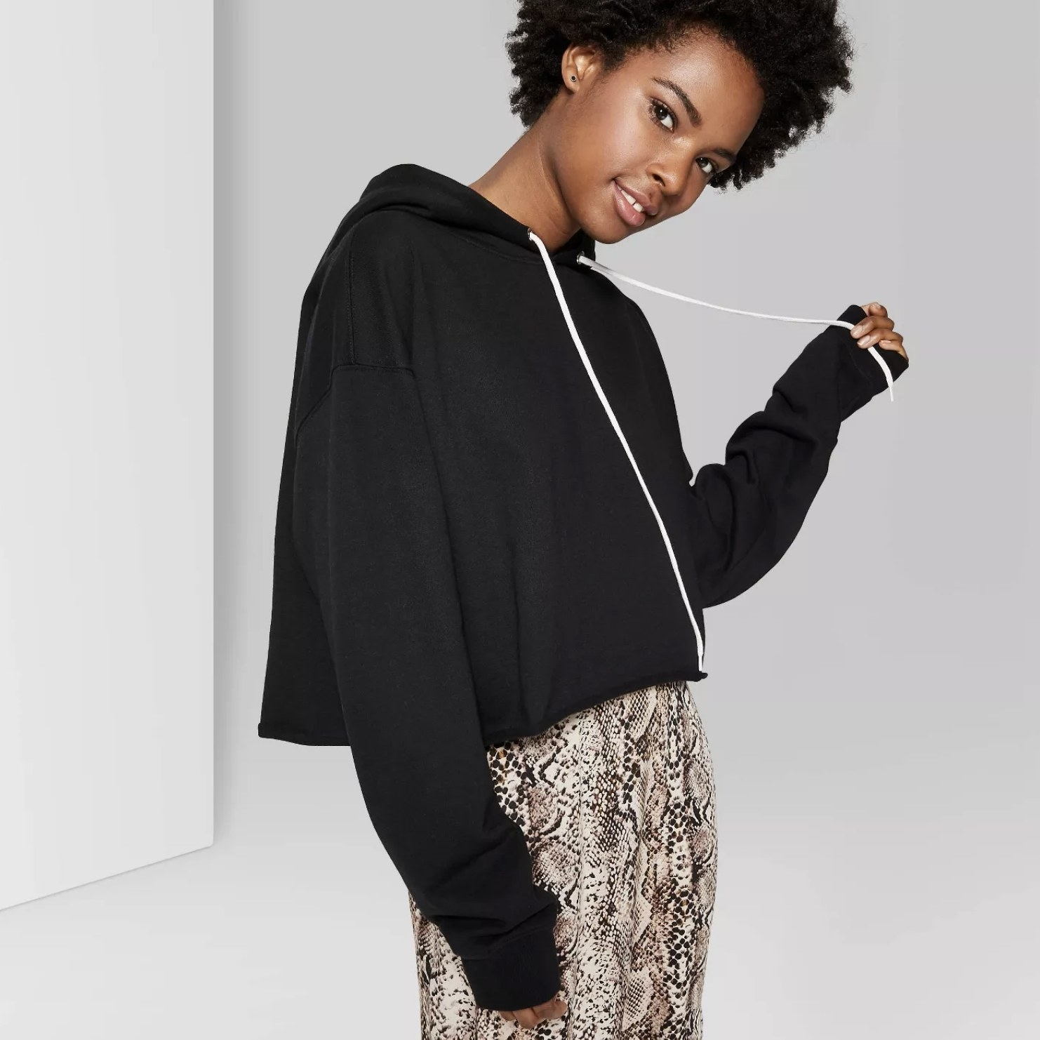 Model is wearing a black cropped hoodie with white drawstrings and a snakeskin skirt