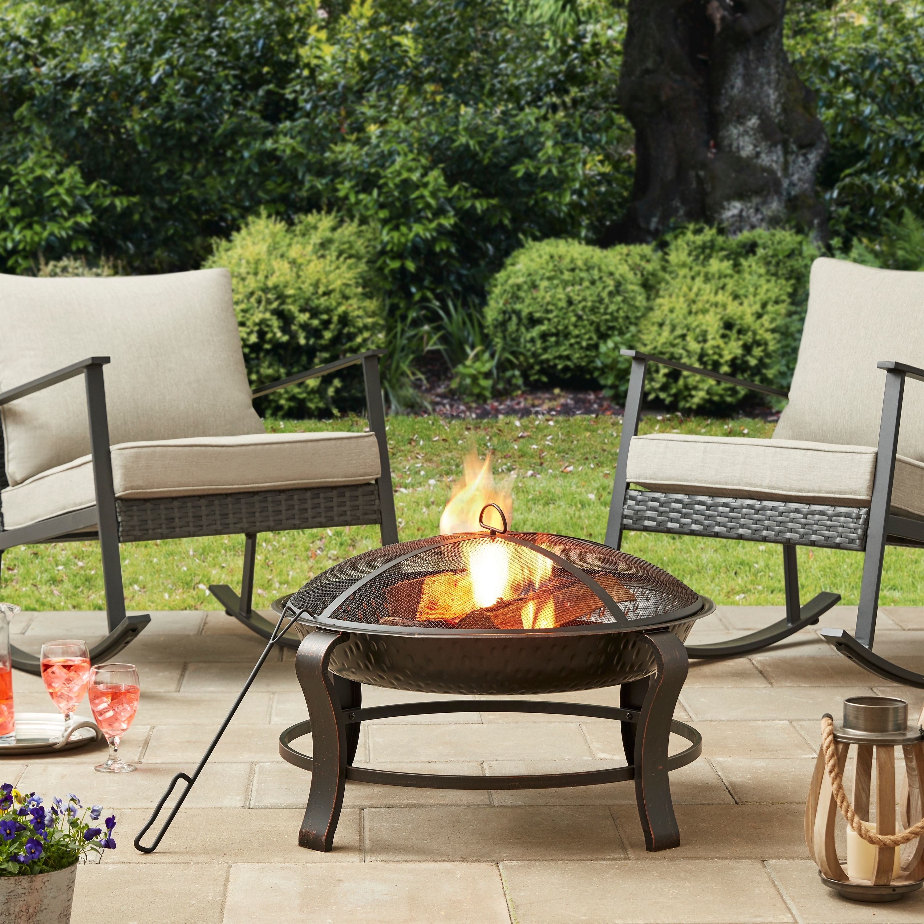 Blazing fire in a bronze frame firepit with poker and mesh cover