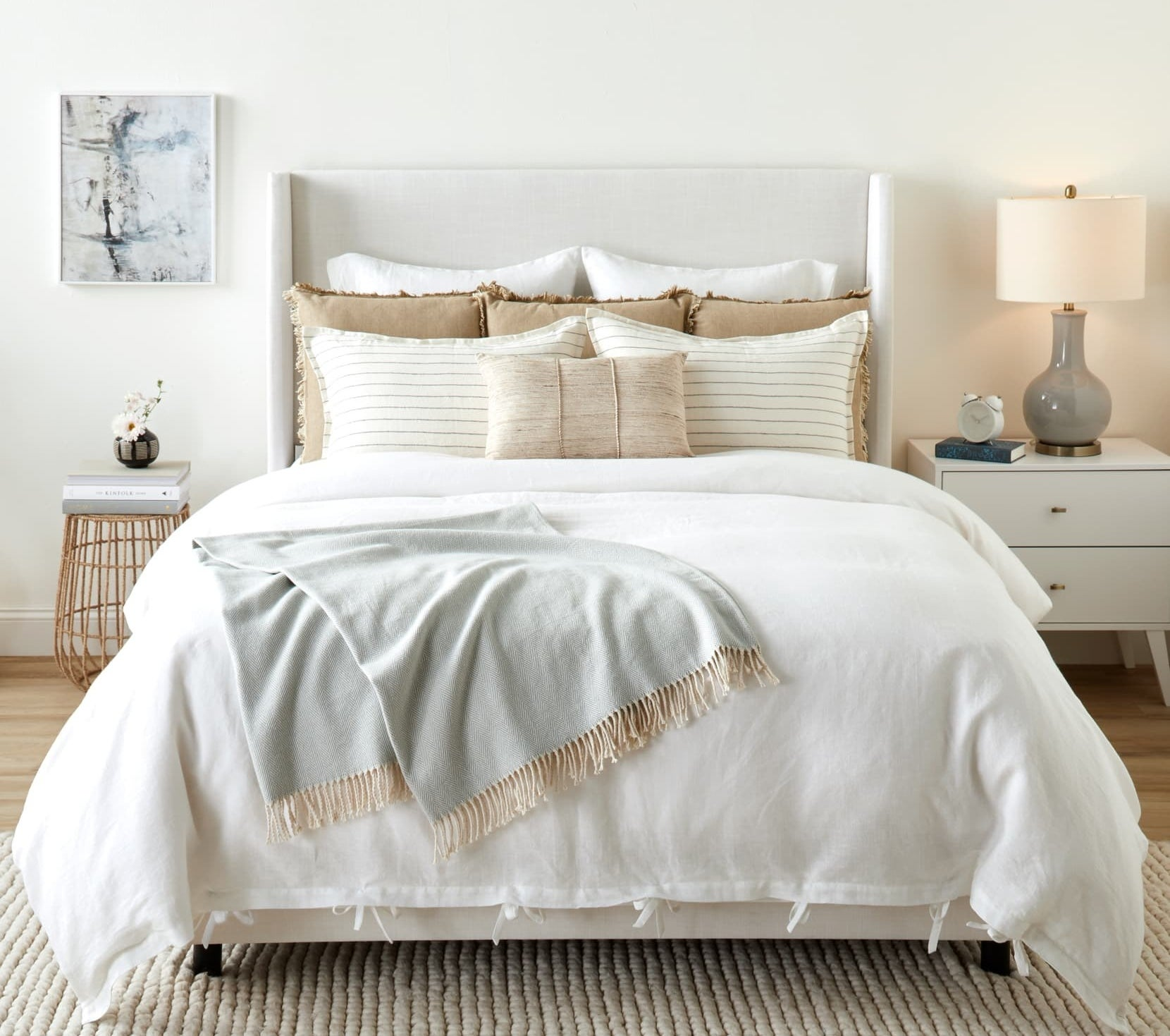 A bed dressed with the sheets and decorative pillows