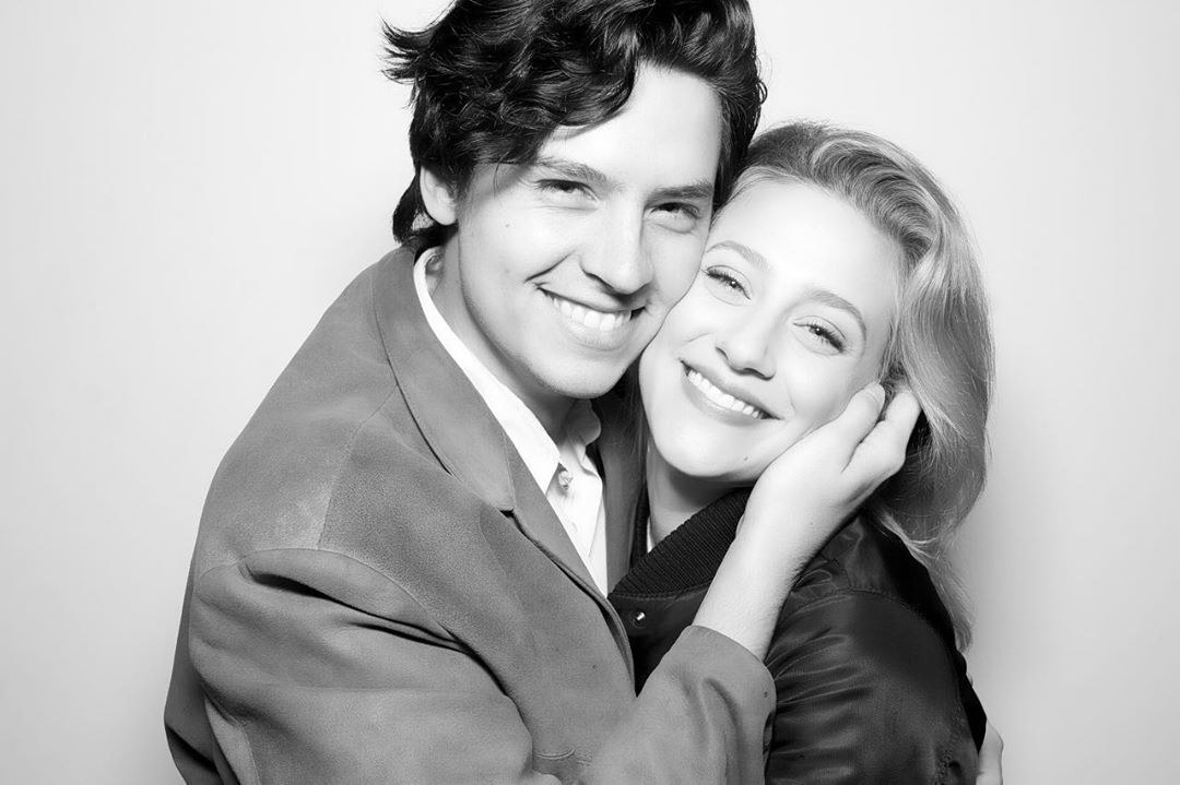 Cole Sprouse holds Lili Reinhart's face as they smile for a picture