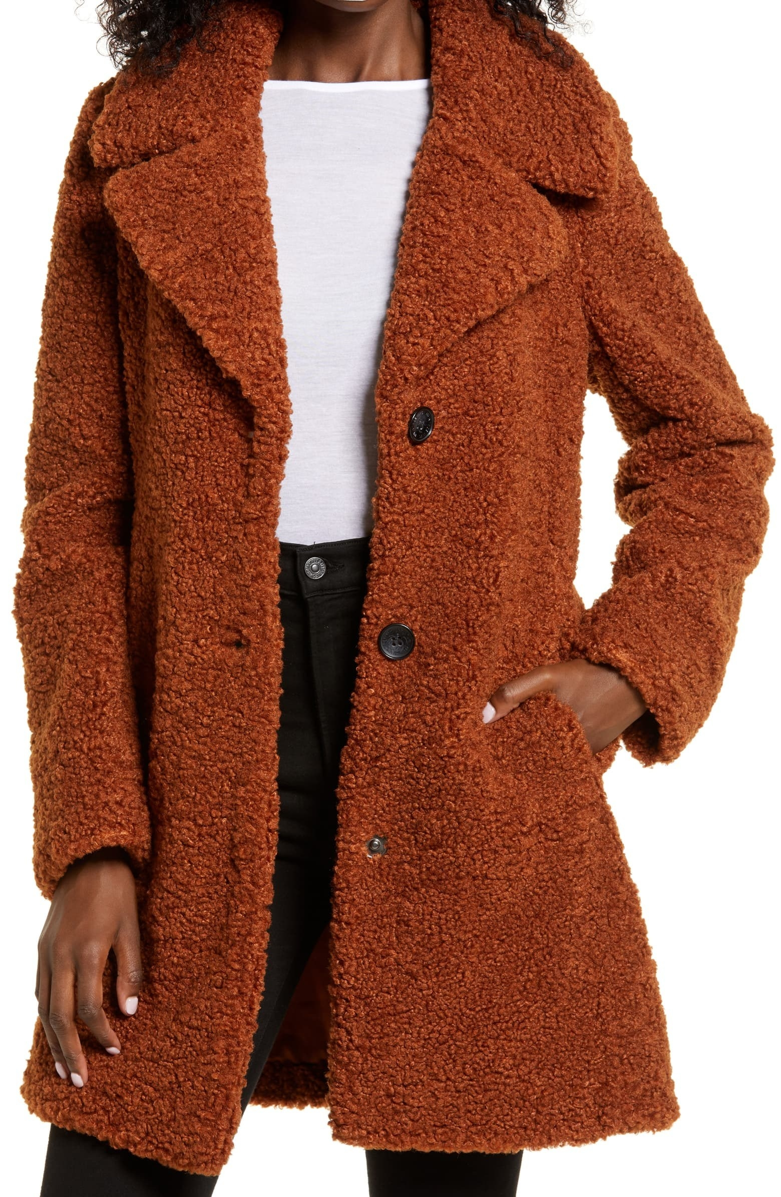 a model in a fuzzy brown/orange coat