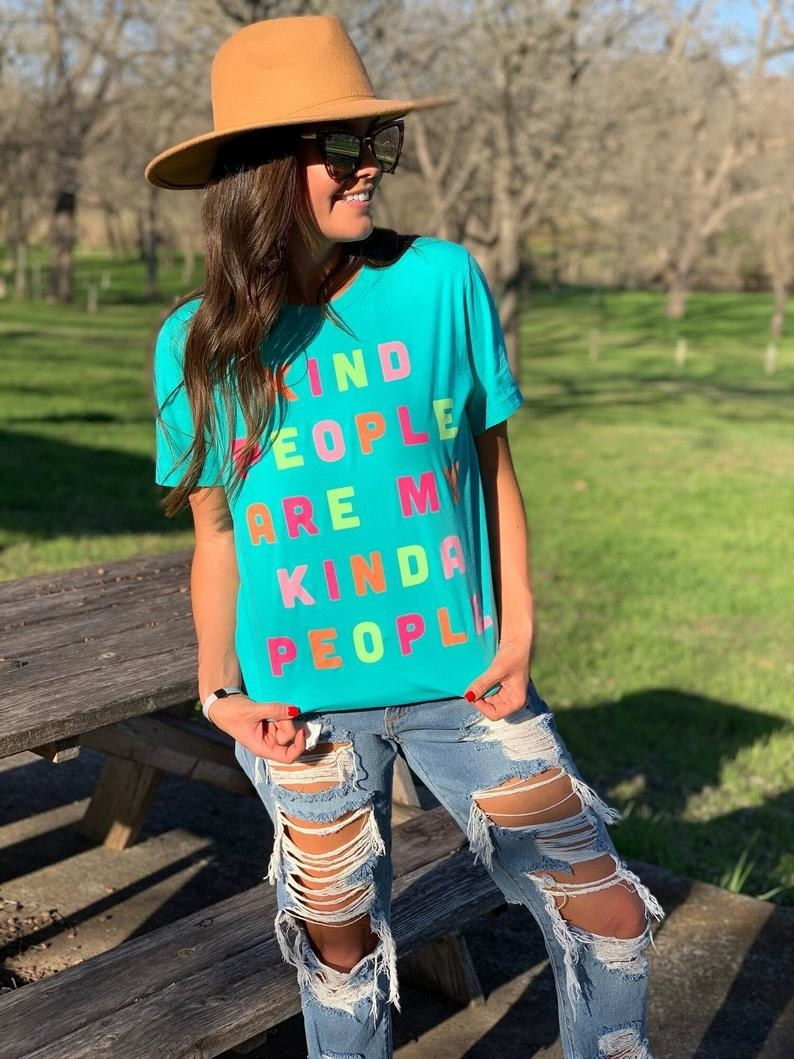 """A model wearing the teal tee that says """"Kind people are my kinda people"""" in neon pink, orange, and yellow letters"""