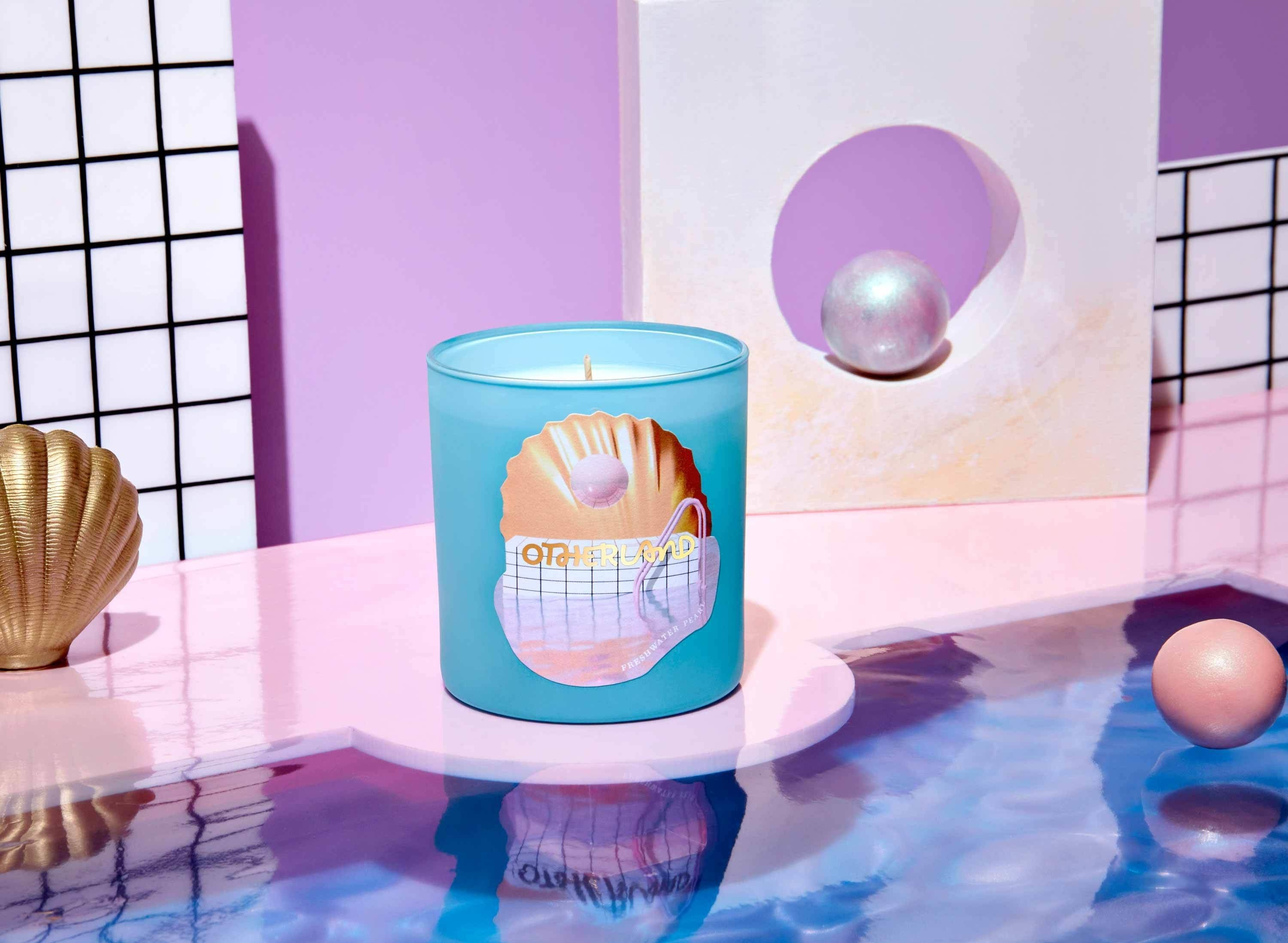 light blue candle with sea shell and pool design label sitting by pool with shells and pearls