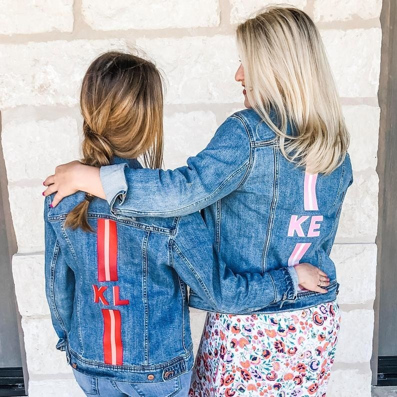 Models wearing the jackets with their initials and a preppy stripe printed on the back