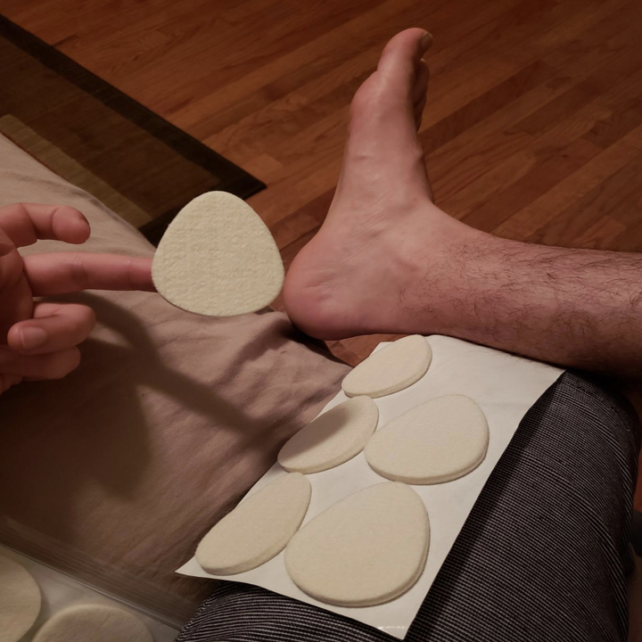 Reviewer image of the adhesive foot pads next to foot to show size. It's about 1/3 the size of this reviewer's foot.