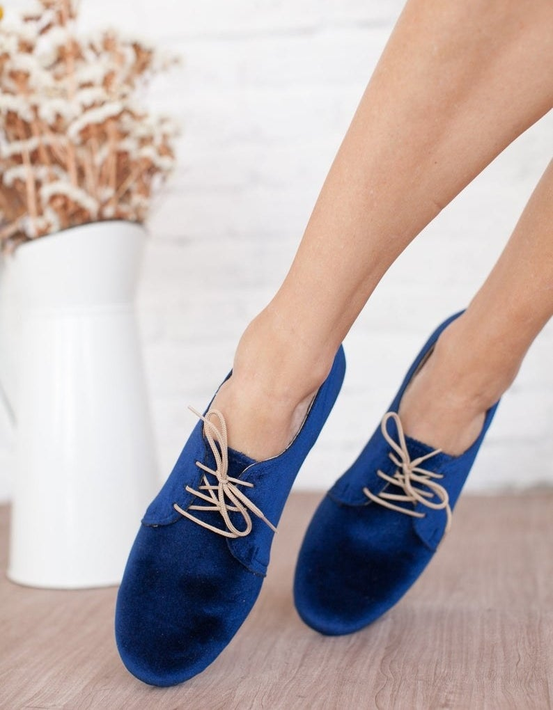A model wearing the round toe, royal blue flats with tan laces