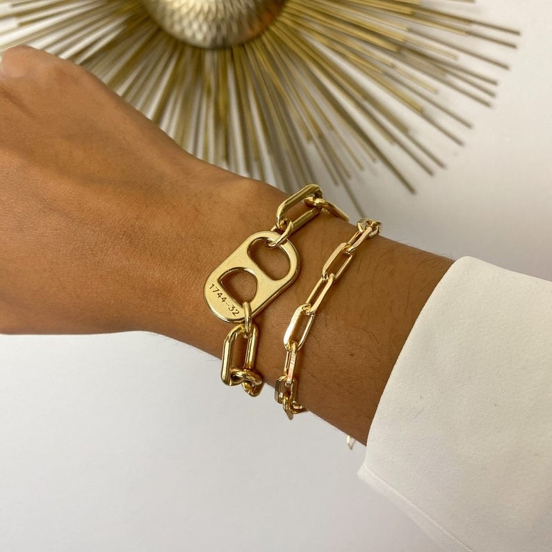 The gold link bracelet with an oversized soda can tab-shaped charm on it stacked with another chain bracelet