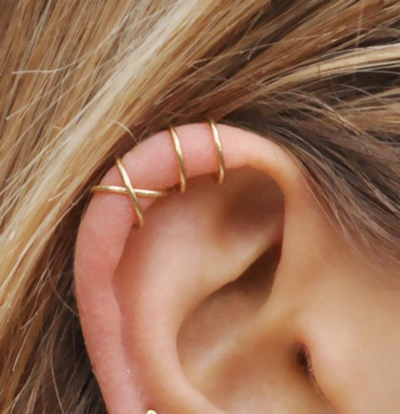 A model's earlobe with both styles of cuff — the crisscross one and the two bar one  — in gold