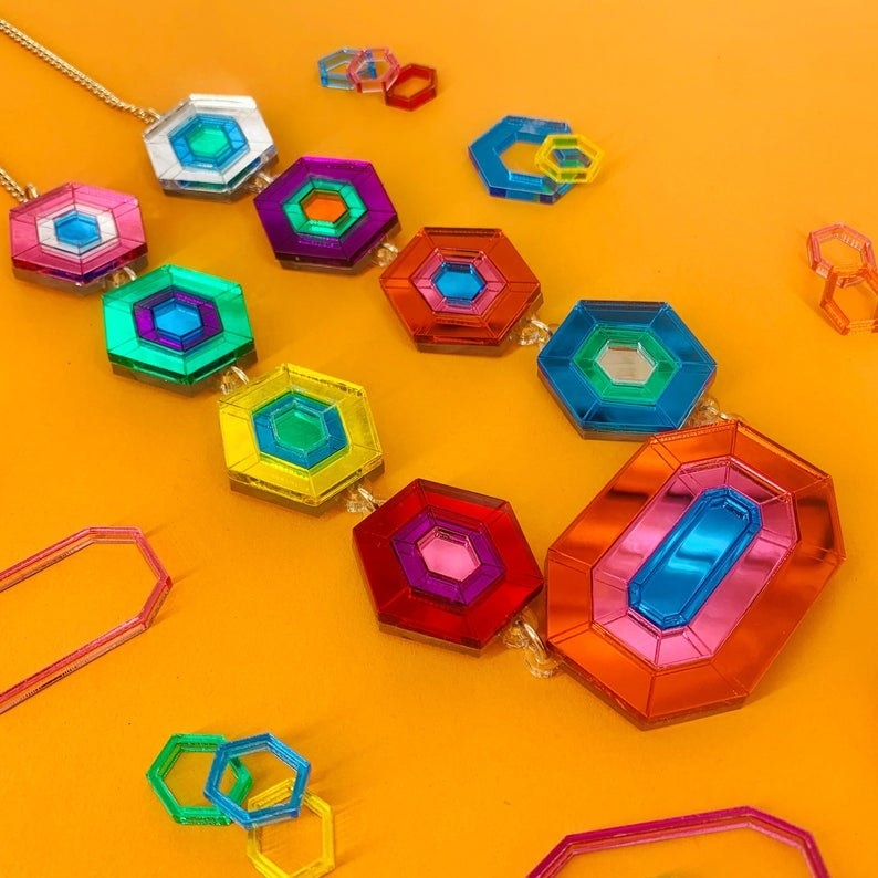 The necklace, with large, colorful, shiny pieces of flat acrylic cut to look like jewels