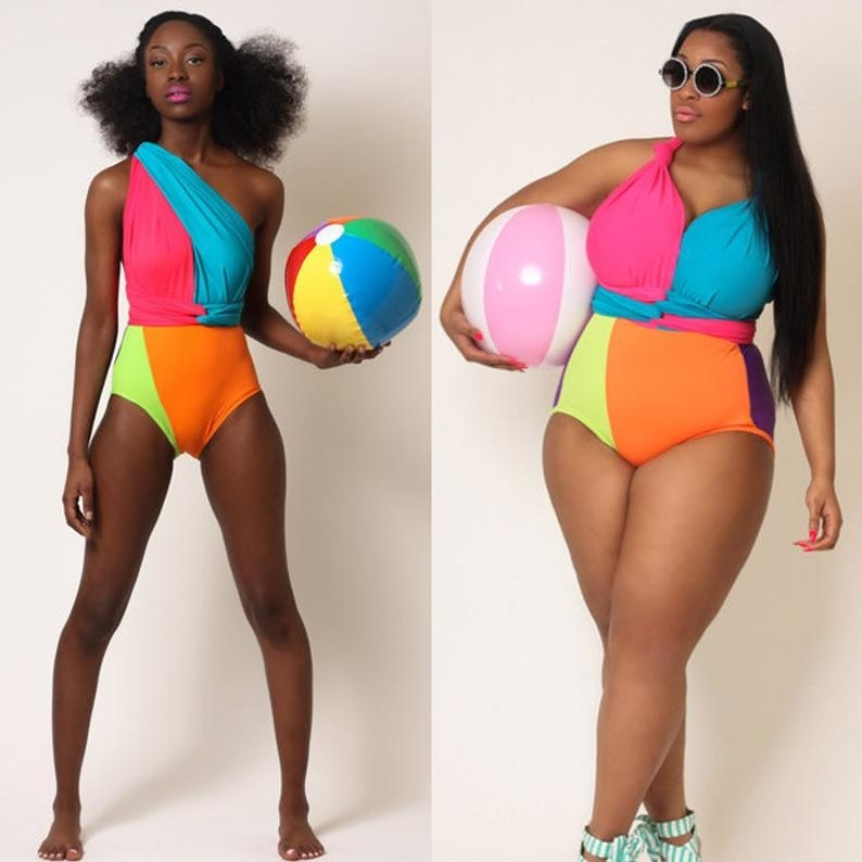Two models wearing the blue, orange, pink, purple, and yellow one-piece suit different ways. One is wearing it in a one-shoulder style while the other has the straps tied into a sweetheart neckline