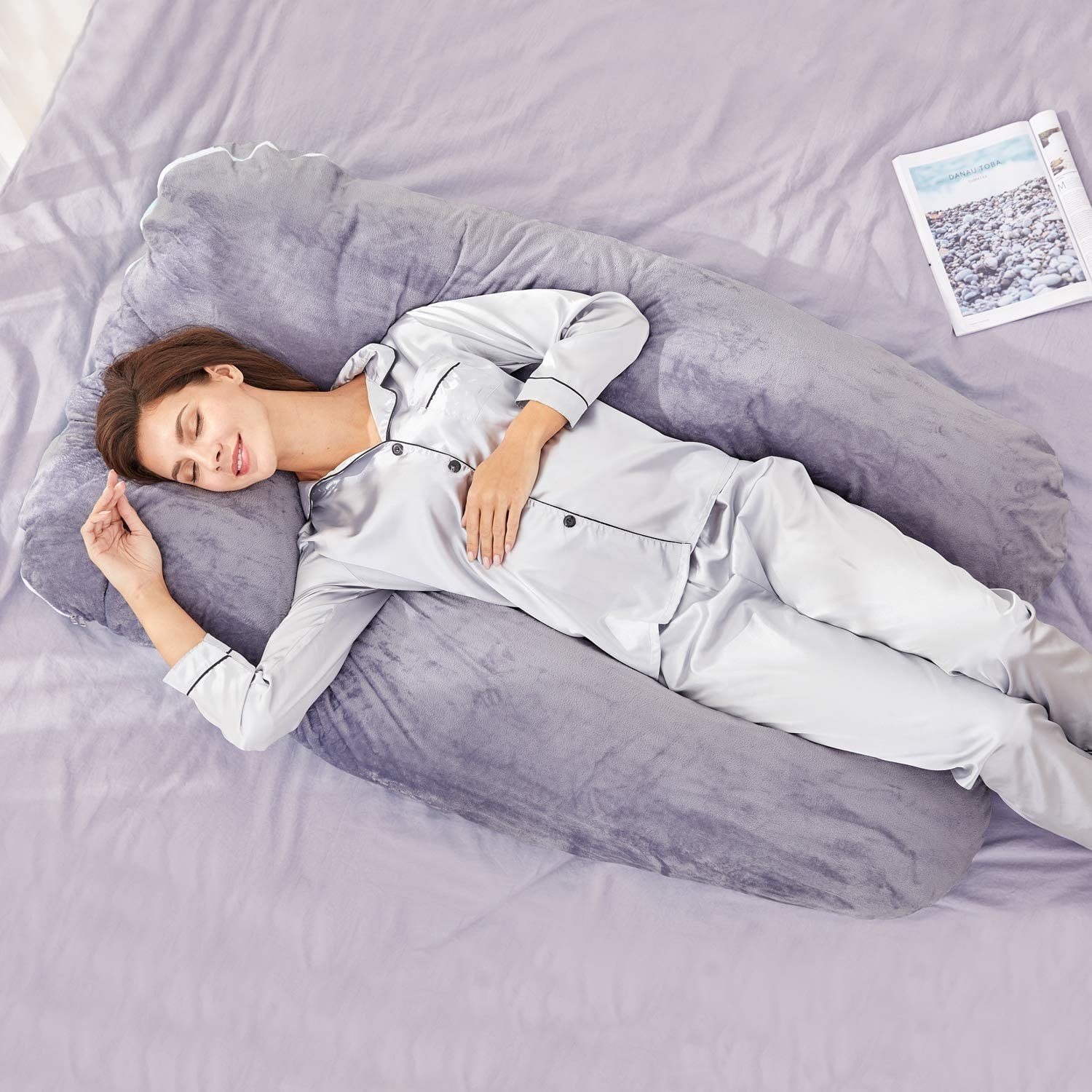 A person lies on a bed supported by a pillow that wraps around their body