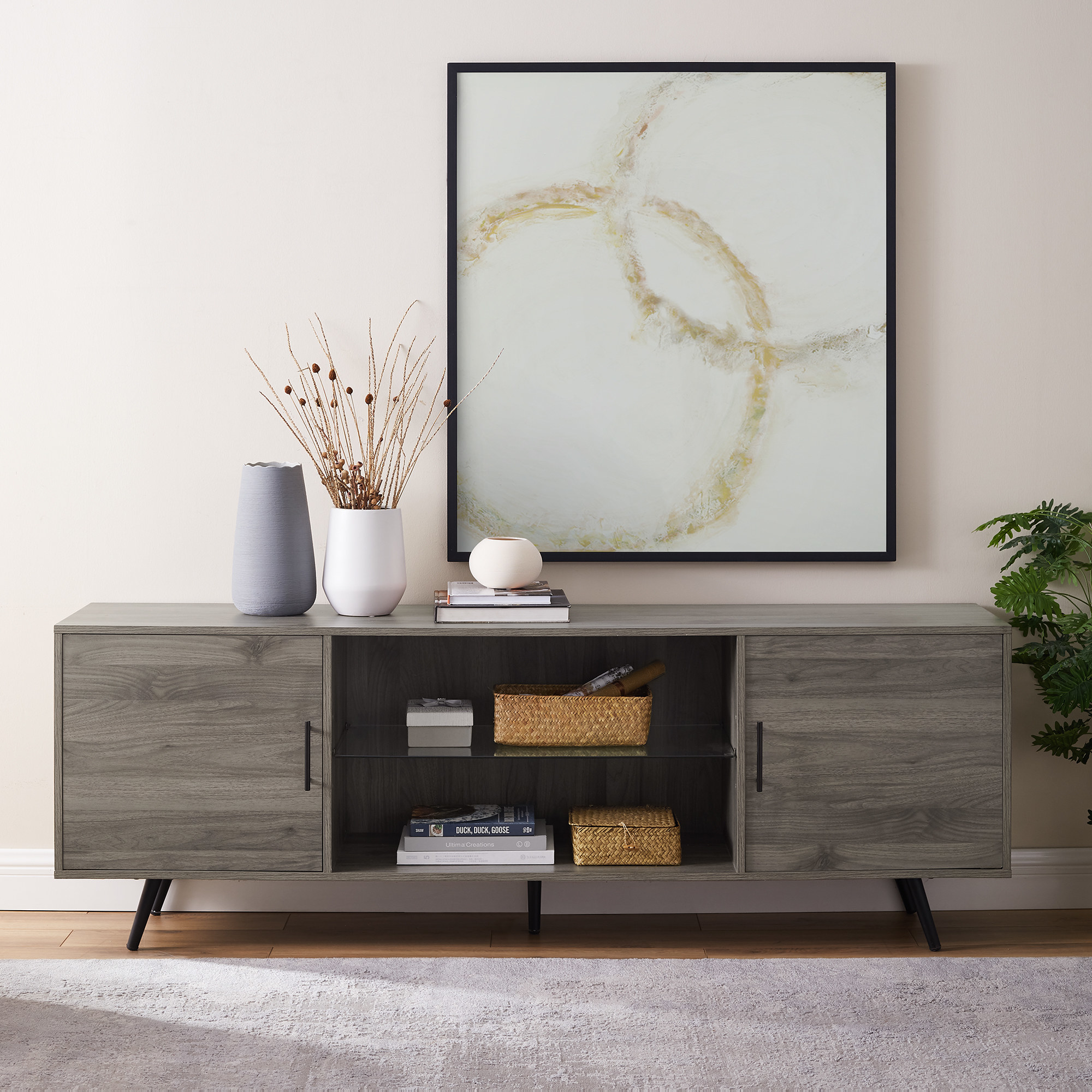 a light brown mid century modern tv stand with two cabinets on each end and a shelf in the middle