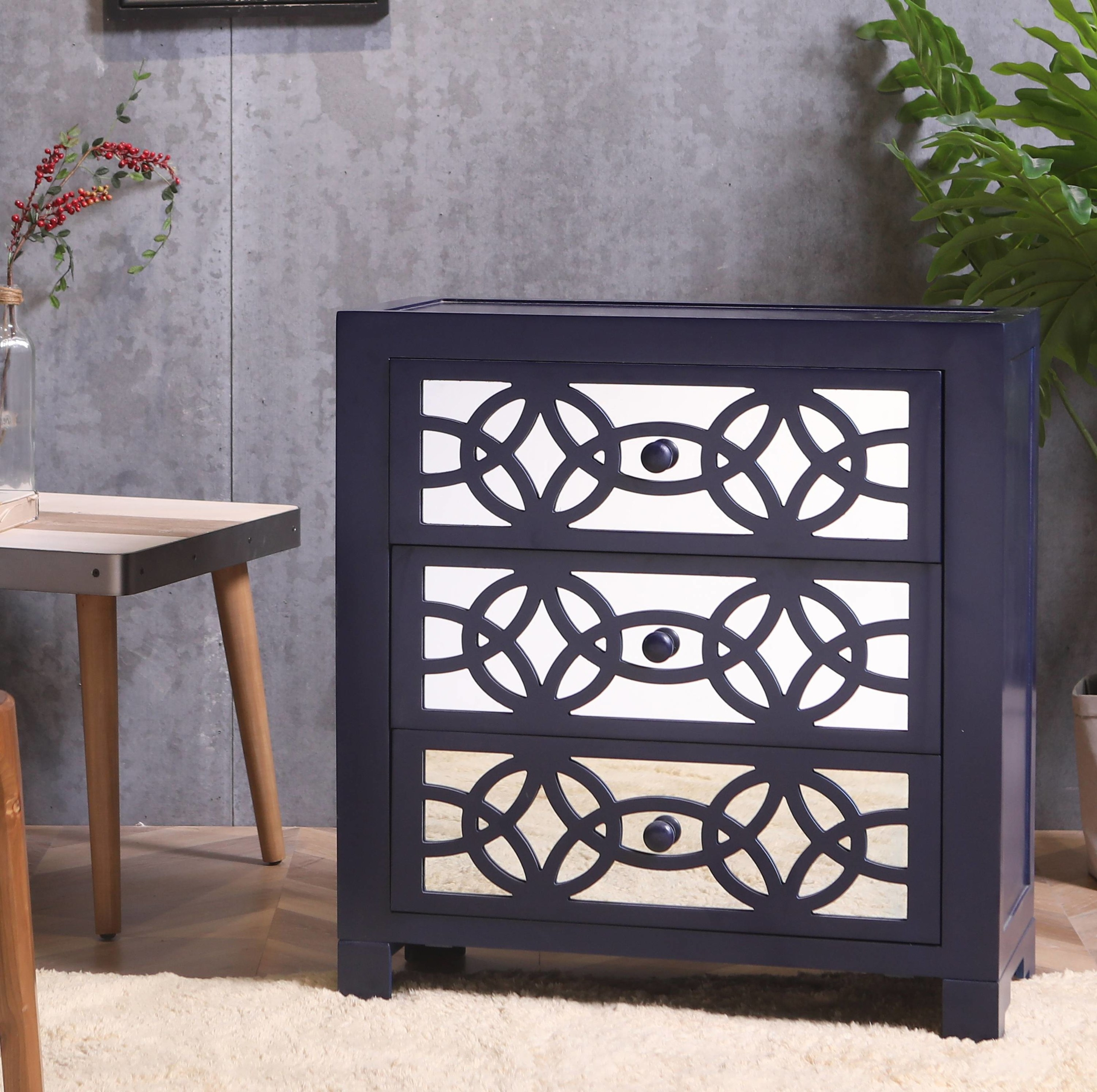 the mirrored cabinet with an intricate design across the three drawers