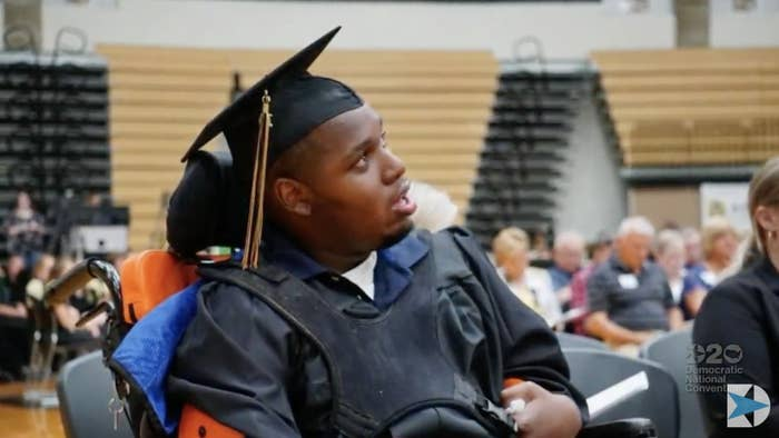 DeAndre Knox wears a graduation cap and gown and sits in a wheelchair in a school gym