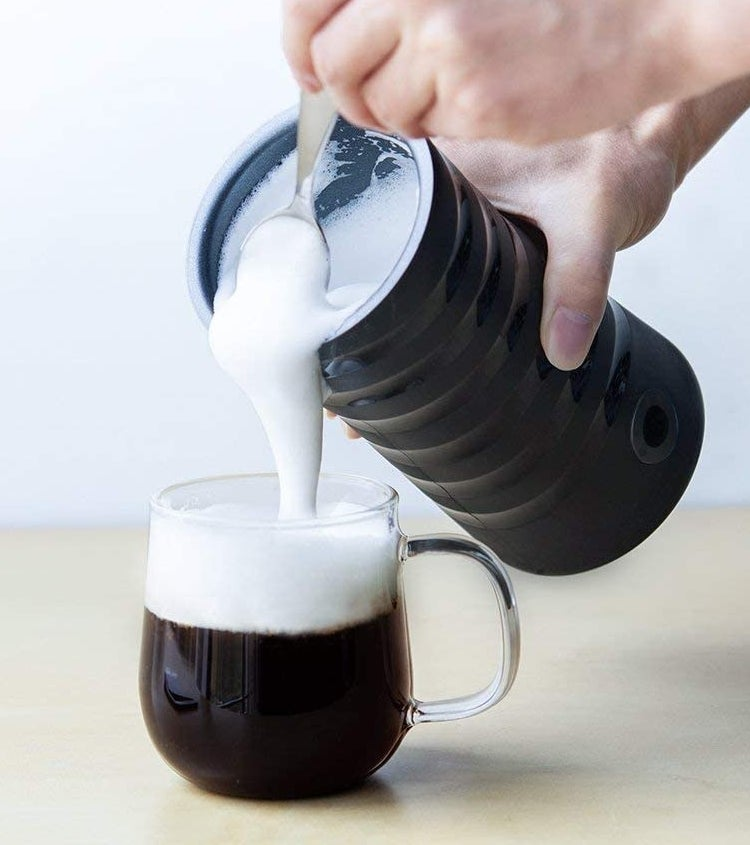 A person pouring foamy milk from the frother into a mug of coffee