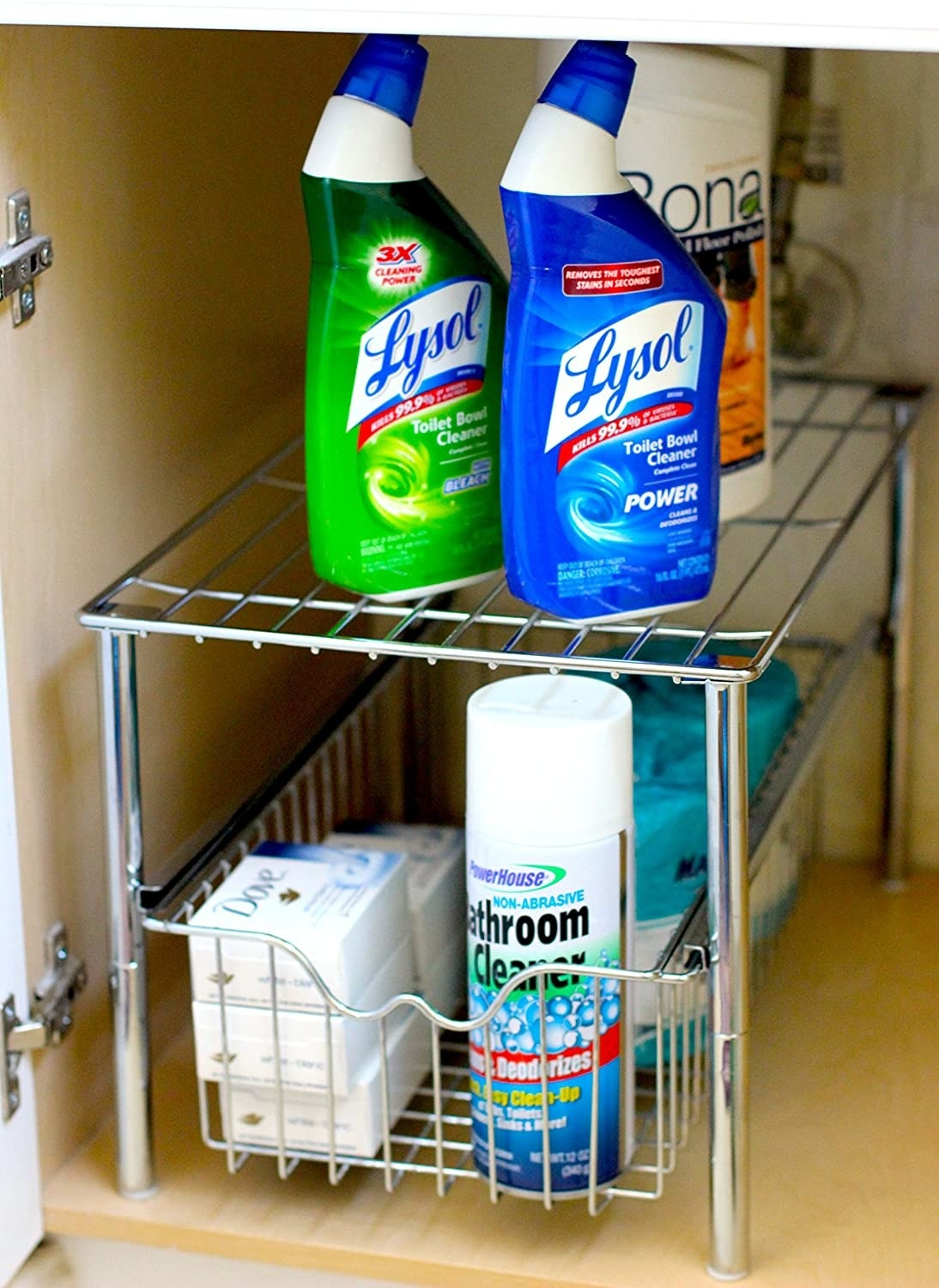 A metal rack with a small basket the bottom that has soap and cleaning products in it There are cleaning products stacked on top of it too