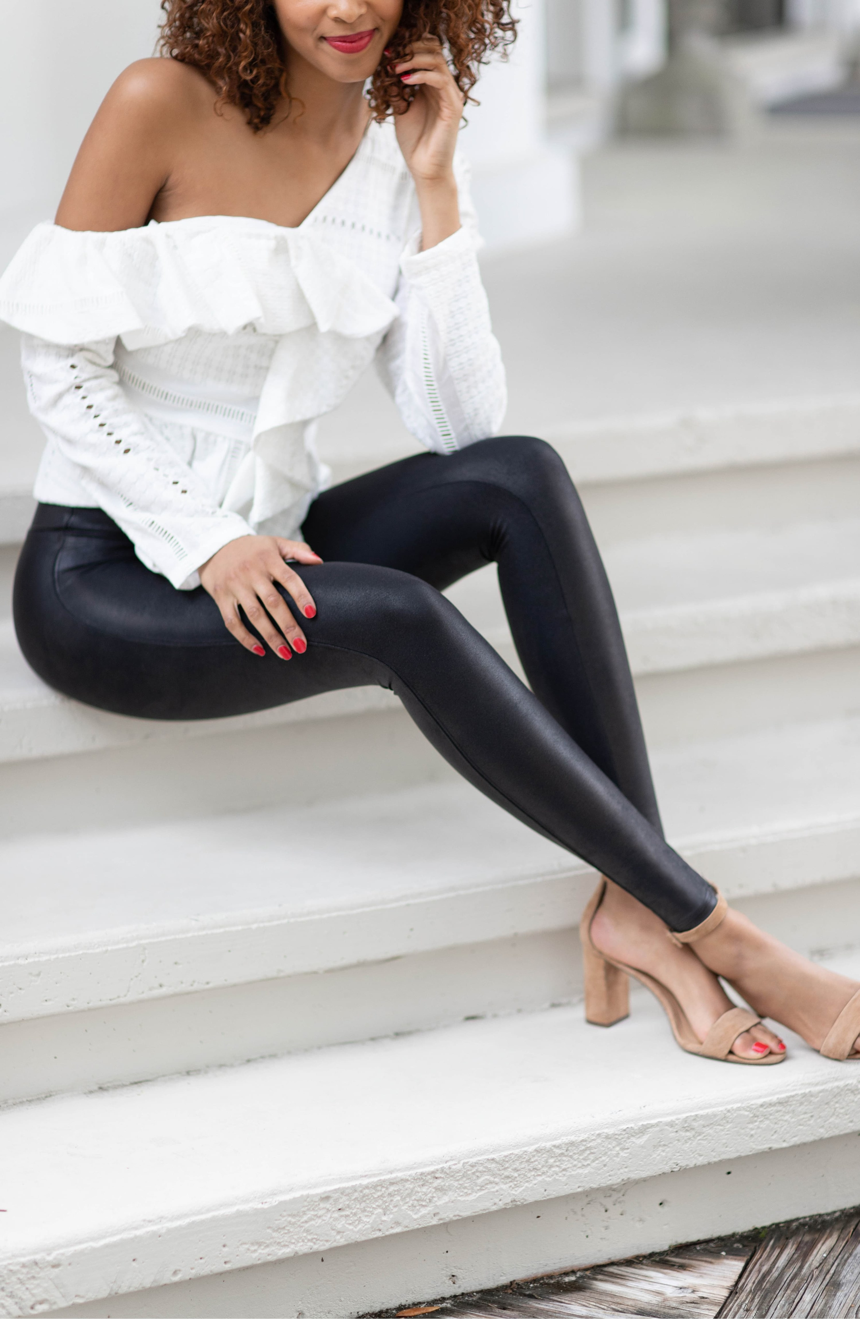 model wearing the leather leggings with nude ankle strap sandals and a white, ruffled, off-shoulder top