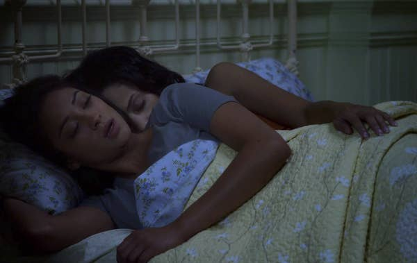 Emily and Maya in her bed at a sleepover spooning as Maya puts her hand on Emily's waist from behind