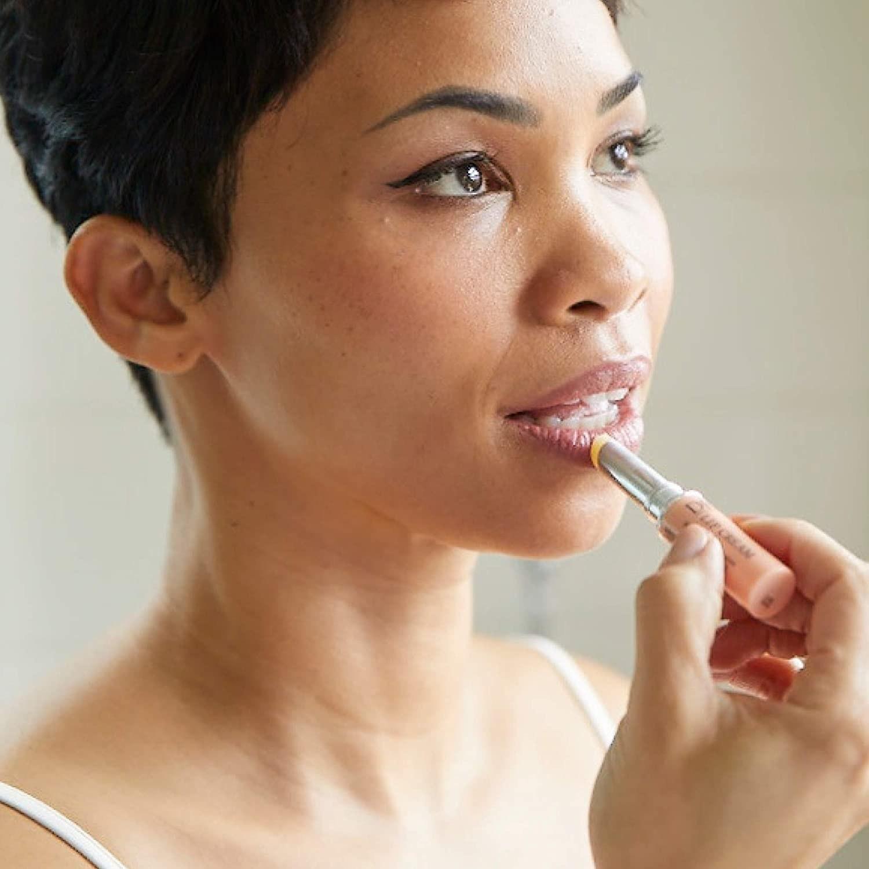 A person applies the lip cream to their lips