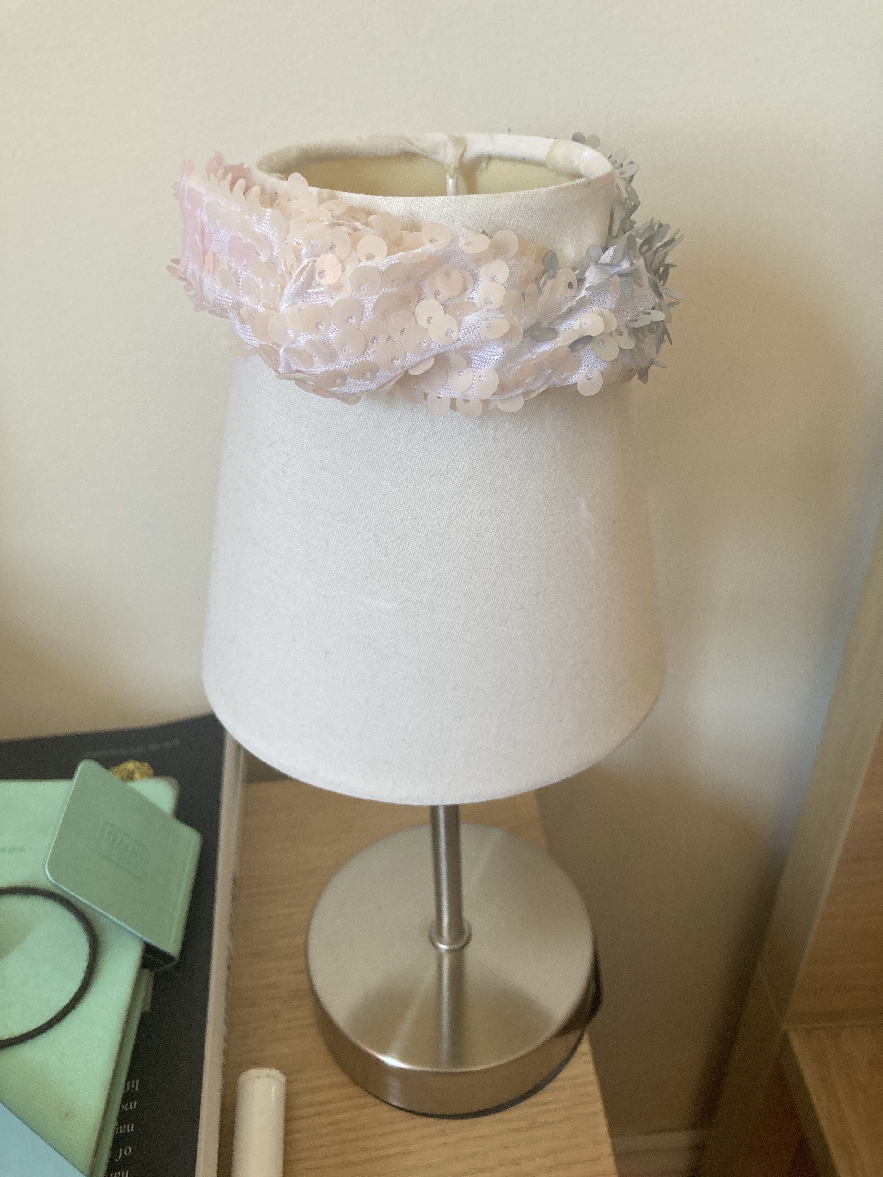 A small desk lamp with a sparkly scrunchie on top