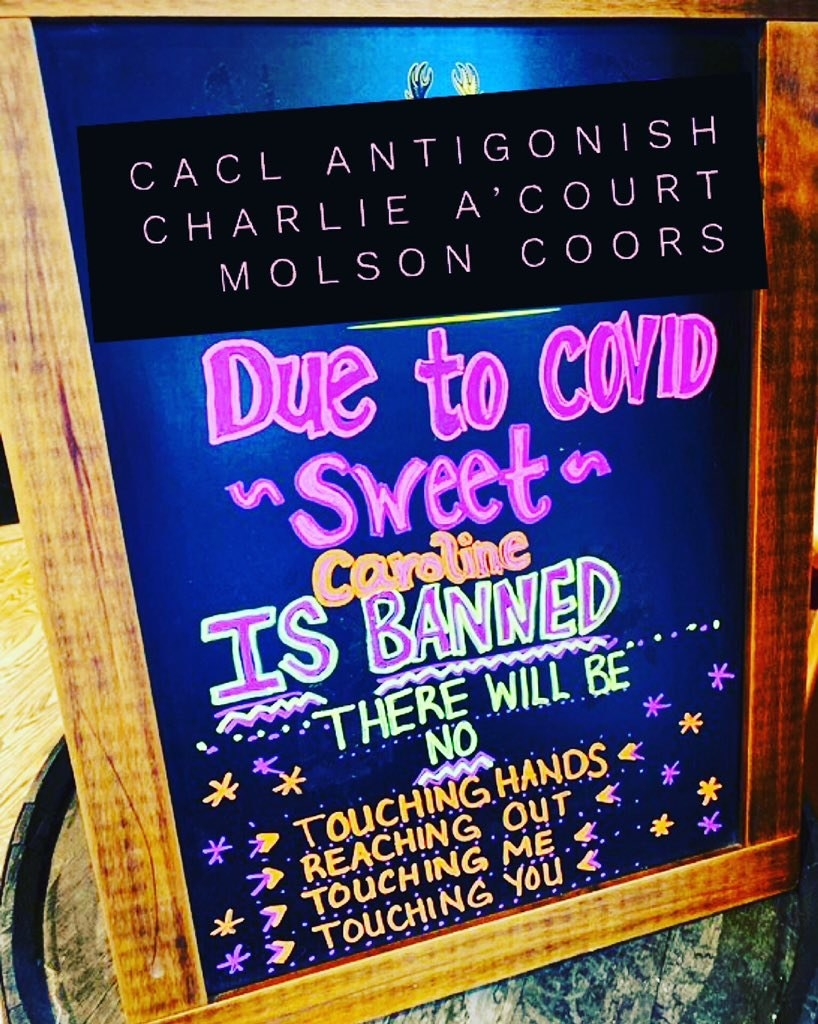 sign reading due to covid sweet caroline is banned no touching hands reachout out