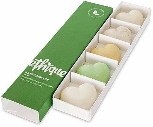a long green box next to a long rectangle insert with five spaces filled with heart-shaped shampoo and conditioner bars