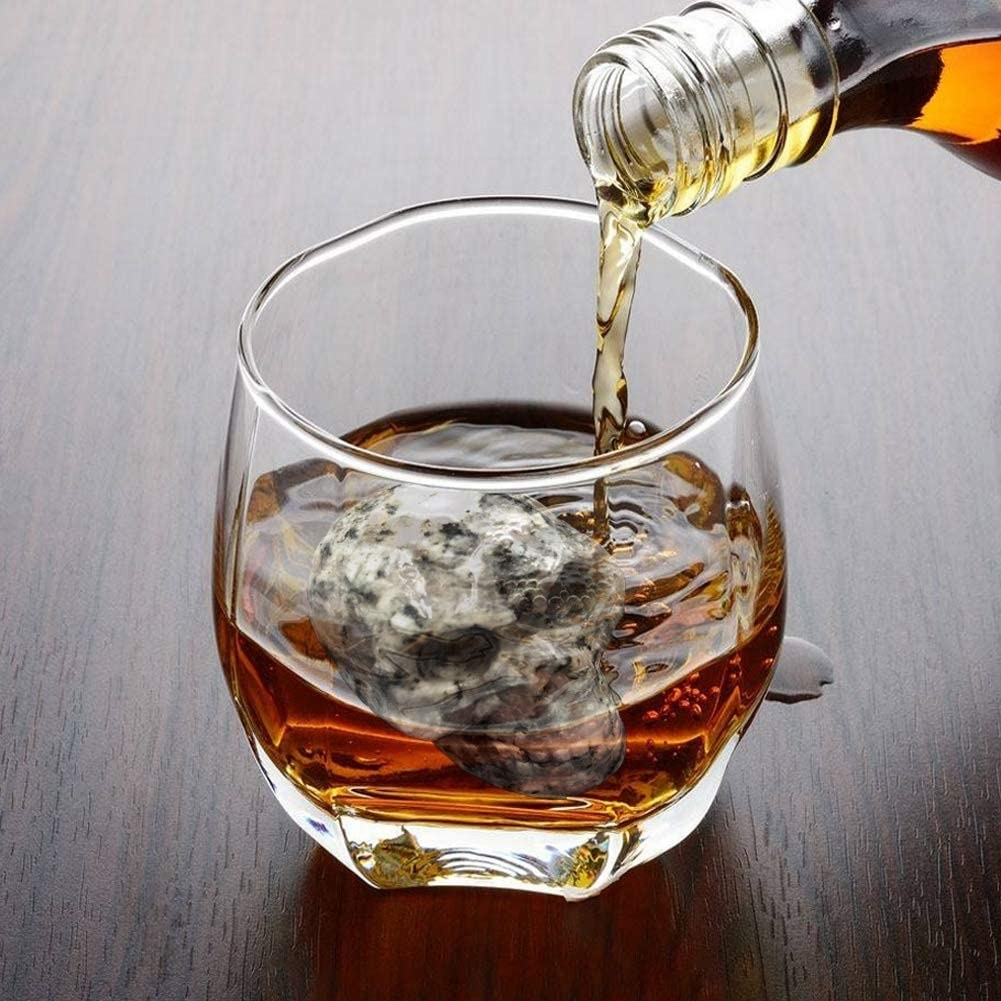 A close up of the skull whiskey stones inside a glass filled with liquor