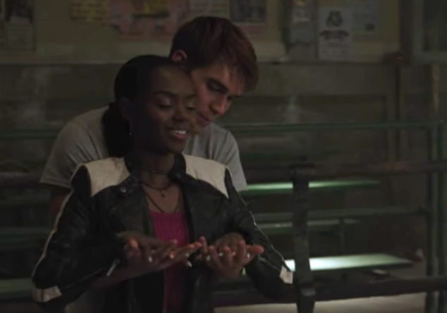 Archie holding Josie from behind as they link hands