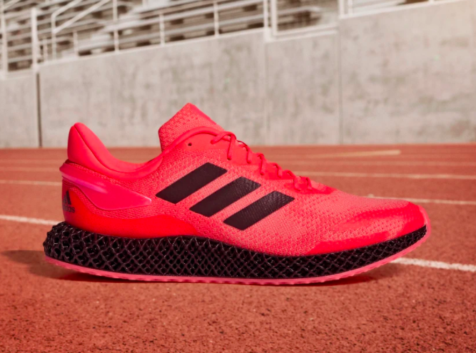 Hot pink Adidas 4D Run 1.0 Shoes on a red track below bleachers