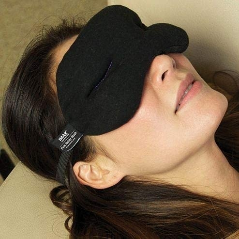 A person lying on the couch while wearing the weighted eye mask