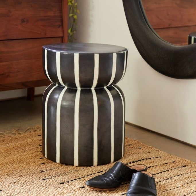 A side table with inverted semicircles and cylindrical pieces in black with white stripes down the sides